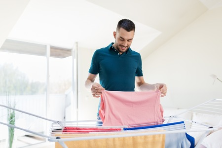 smiling man with laundry and drying rack at home