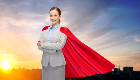 businesswoman in superhero cape over city sunset 스톡 콘텐츠