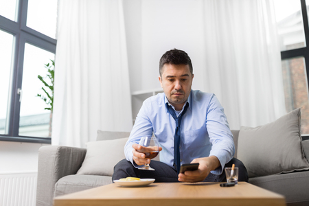 drunk man with smartphone and alcohol at home