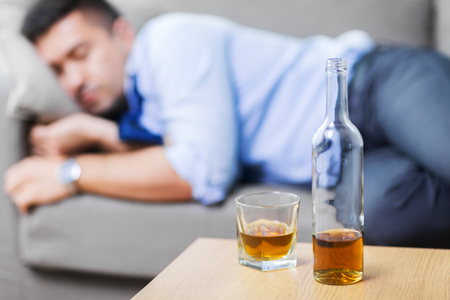 bottle of alcohol on table and sleeping drunk man