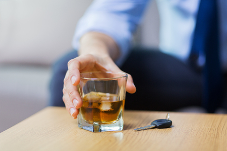 close up of hand with alcohol and car key on table Stock Photo