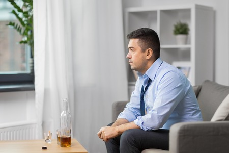 alcoholic with bottle drinking whiskey at home