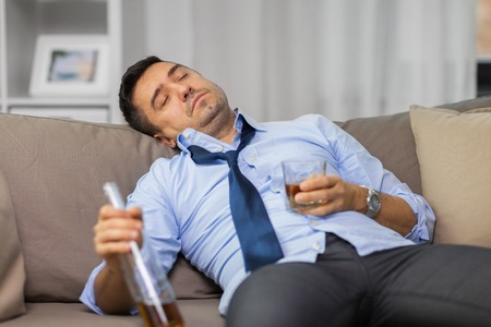 drunk man with bottle of alcohol sleeping at home Stock Photo
