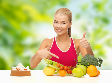 diet and eating concept - woman with vegetables and cake choosing healthy food over green natural background