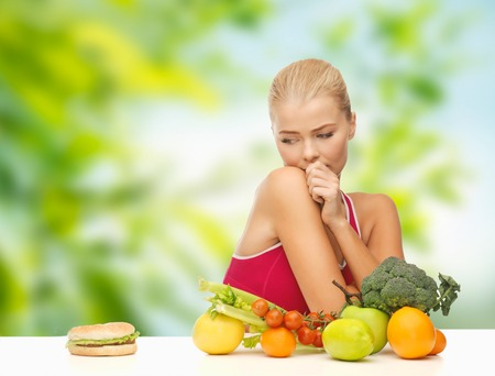 diet, junk food and eating concept - doubting woman with fruits and vegetables looking at hamburger over green natural background