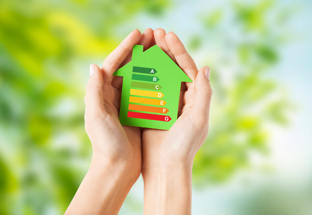 efficiency  and home concept - closeup of female hands holding green paper house with energy saving rating over natural background