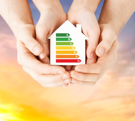 efficiency and home concept - close up of female hands holding paper house with energy saving rating over evening sky background