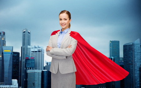 business, woman power and people concept - smiling businesswoman in red superhero cape over singapore city skyscrapers background