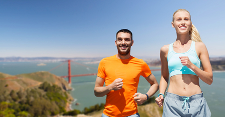 fitness, sport and healthy lifestyle concept - smiling couple running over golden gate bridge in san francisco bay background Stock Photo
