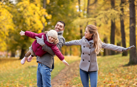 family, season and people concept - happy mother, father and little daughter playing at autumn park