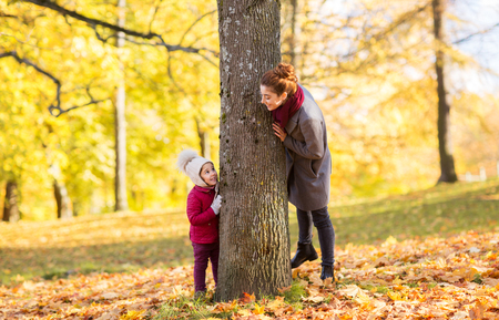 family, season and people concept - happy mother and little daughter at tree trunk playing in autumn park Reklamní fotografie
