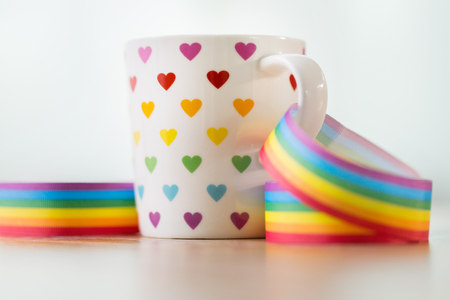 homosexual and lgbt concept - close up of cup with rainbow colored heart pattern and gay pride awareness ribbon on wooden table Foto de archivo - 103398393