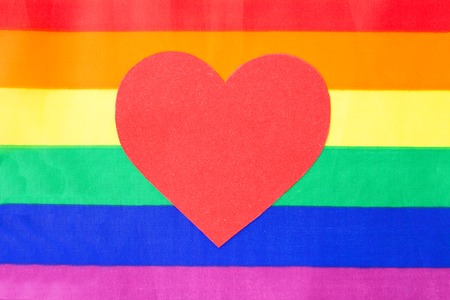 gay pride, homosexual and lgbt concept - red heart over rainbow background