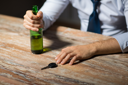 close up of hands with alcohol and car key