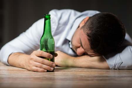 drunk man with beer bottle lying on table at night Standard-Bild - 103423411