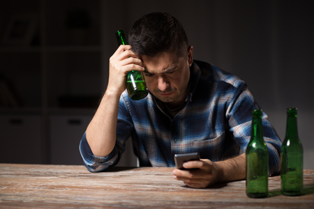 man with smartphone and bottle of beer at night Stock Photo - 103423414