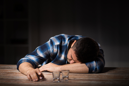 drunk man with empty glasses on table at night Stock Photo