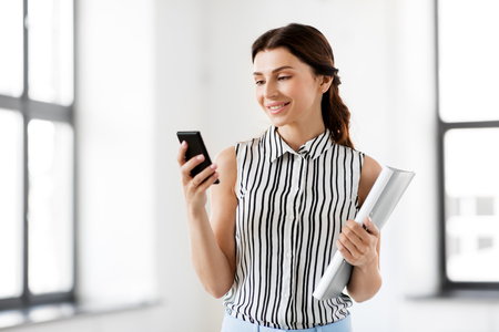 businesswoman with smartphone and folder at office Banco de Imagens