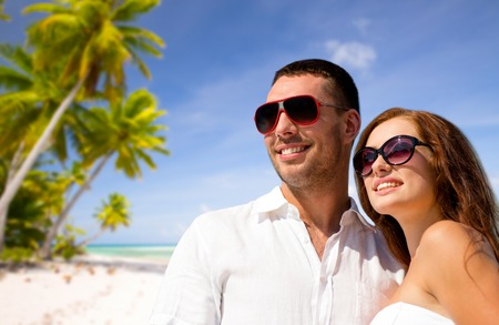 happy couple in sunglasses over tropical beach