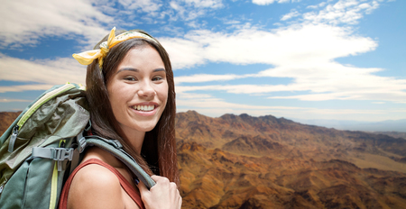 happy woman with backpack over grand canyon