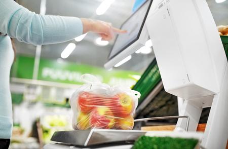 Mujer pesando manzanas a escala en la tienda
