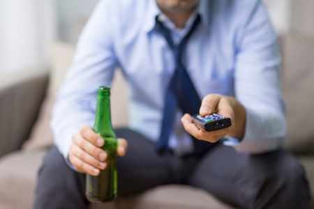 close up of man with tv remote drinking beer Reklamní fotografie