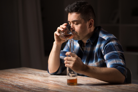alcoholic with bottle drinking whiskey at night