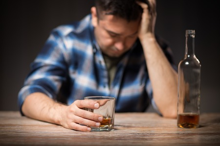 alcoholic with glass drinking whiskey at night Stock Photo