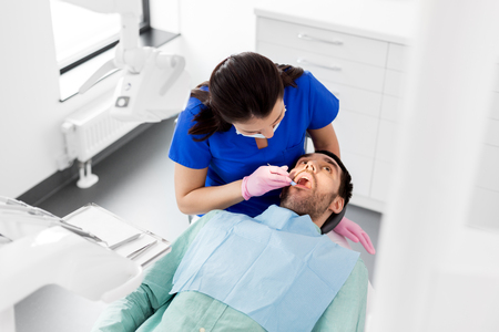 female dentist checking up male patient teeth