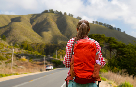 woman with backpack traveling over big sur hills