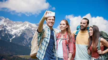 friends with backpack taking selfie by smartphone