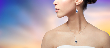 close up of woman with earring and pendant Banco de Imagens