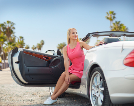 woman posing in convertible car over venice beach Stock Photo