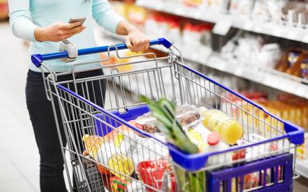 Frau mit Smartphone, die Lebensmittel im Supermarkt kauft