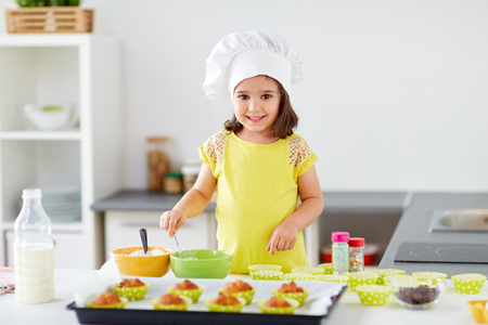little girl in chefs toque baking muffins at home Reklamní fotografie - 103934665