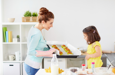 mother and daughter baking muffins at home