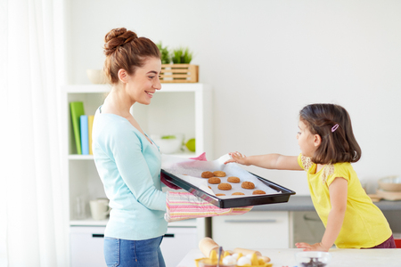 happy mother and daughter baking cookies at home Banco de Imagens