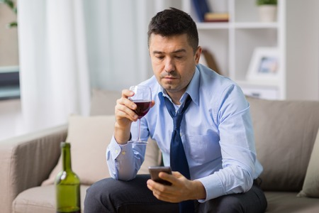 drunk man with alcohol and smartphone at home