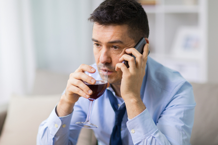 drunk man with alcohol calling on smartphone Stock Photo