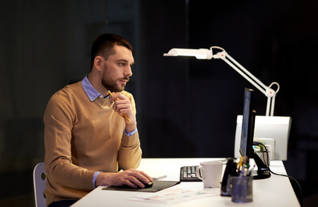 man with computer working late at night office Stock Photo