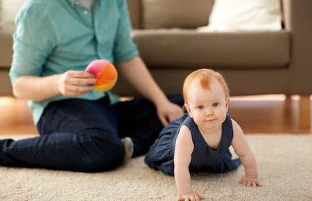 little red haired baby girl and father at home