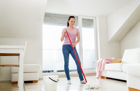woman or housewife with mop cleaning floor at home Фото со стока