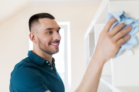 man cleaning shelf with cloth at home Stock Photo