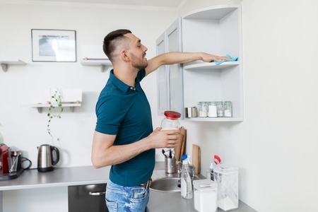 man with rag cleaning kitchen cupboard at home Stock Photo