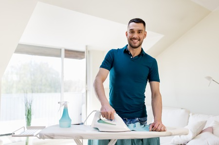 smiling man ironing shirt by iron at home