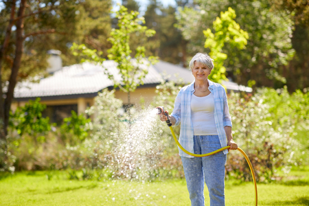 senior woman watering lawn by hose at garden Archivio Fotografico - 103935382