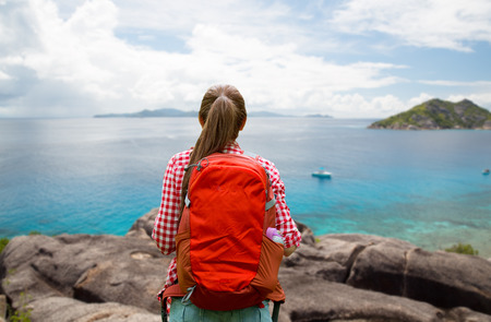 woman with backpack over seychelles island