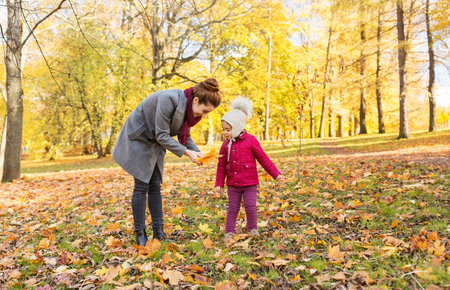 happy family with autumn leaves at park Stock Photo