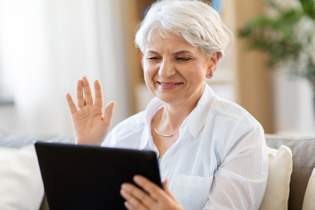 senior woman having video chat on tablet pc Foto de archivo