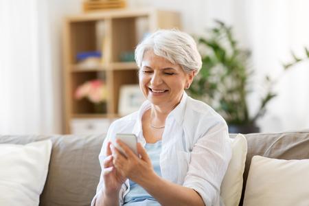 gelukkig senior vrouw met smartphone thuis Stockfoto